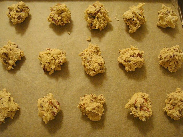 Unbaked cookies lined up on parchment paper ready to go in the oven