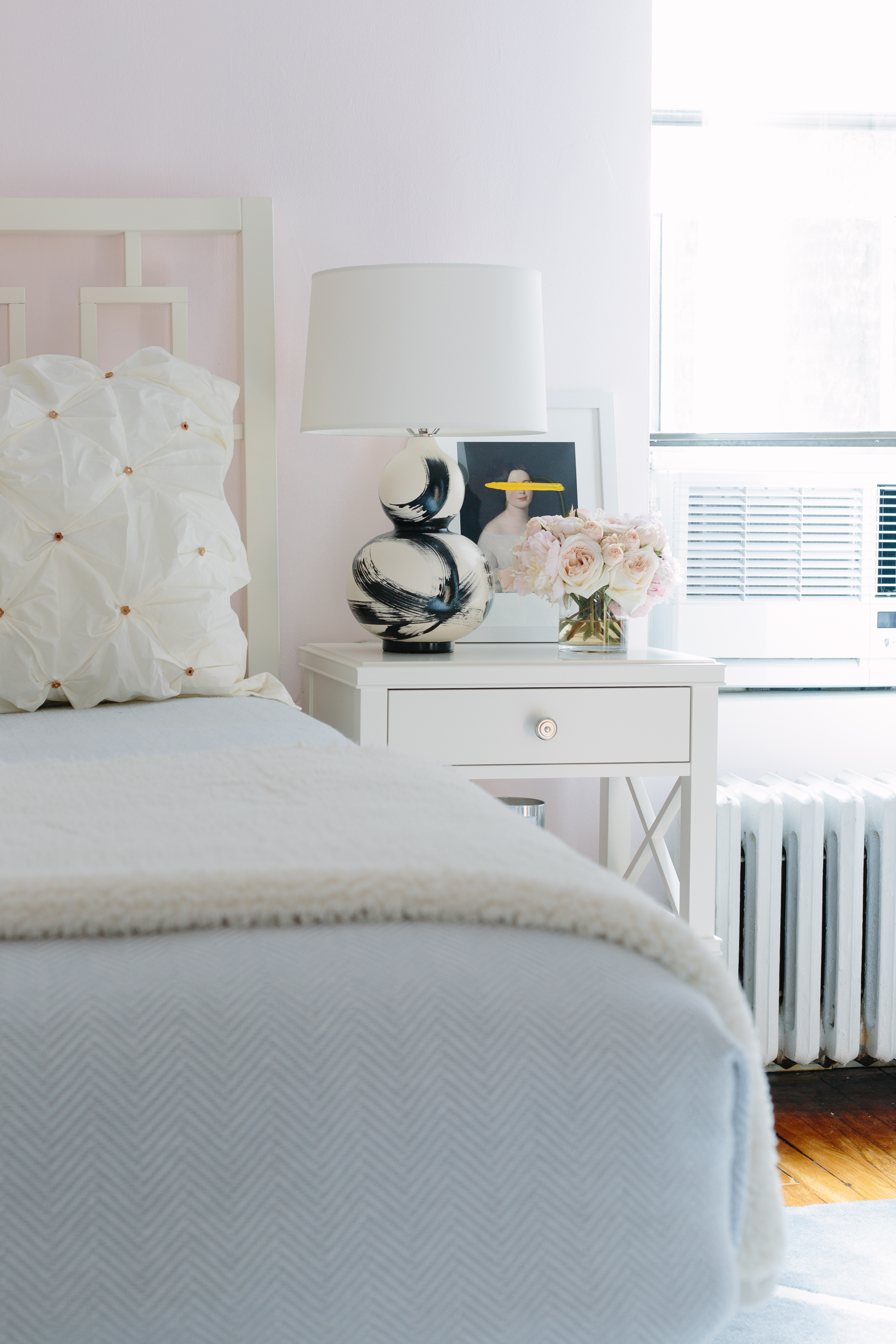 Jana Bek brushstroke lamp in black sits on a Pottery Barn nightstand in a New York City bedroom