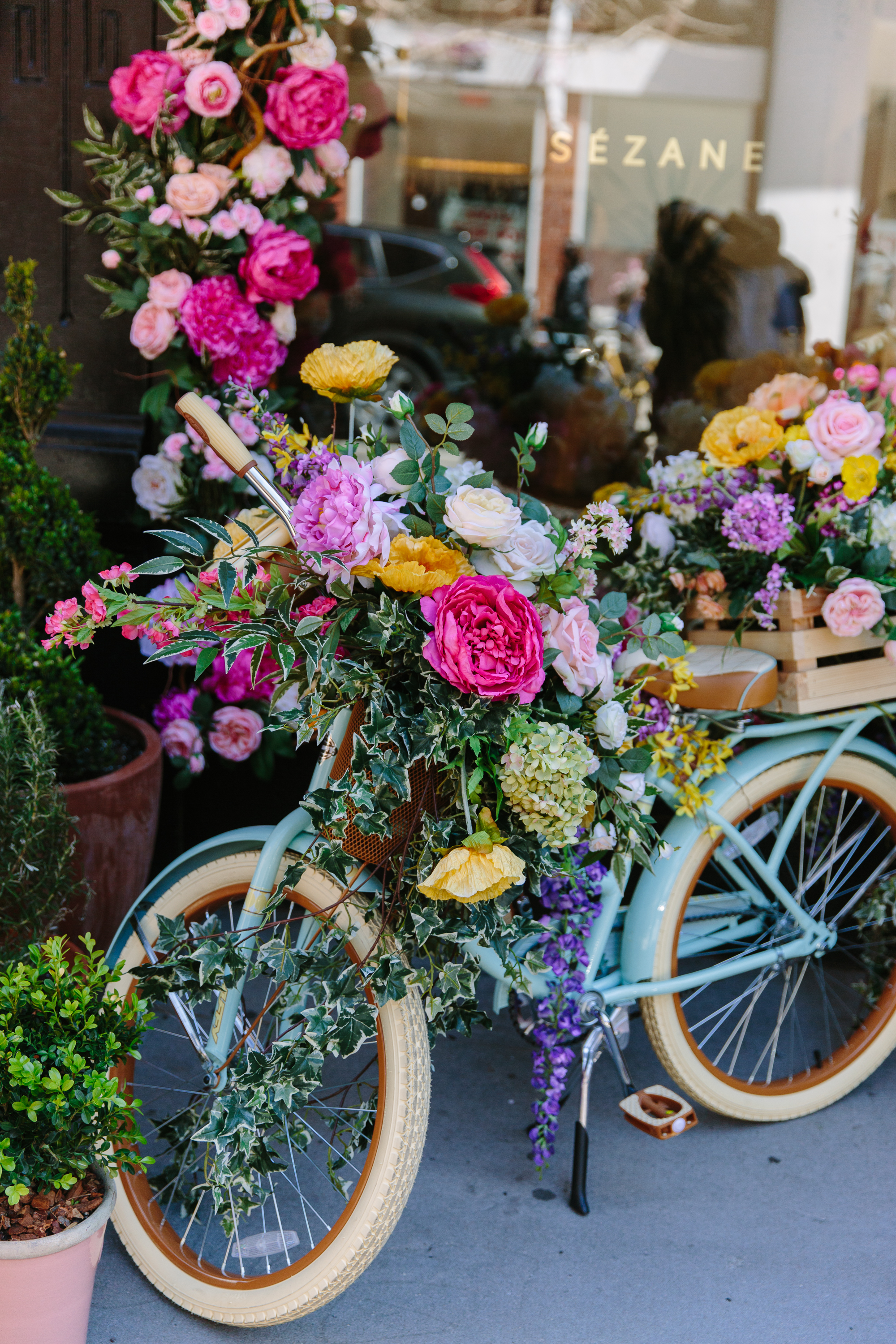 Sezane NYC Floratorium spring storefront bicycle with flowers in basket