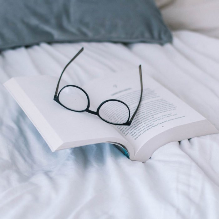 glasses on an open book - New books to read featured by top US life and style blog, York Avenue